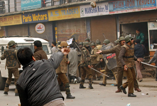 A supporter of the Jammu Kashmir Liberation Front (JKLF) throws a piece of brick towards Indian policemen during clashes in Srinagar December 7, 2012.