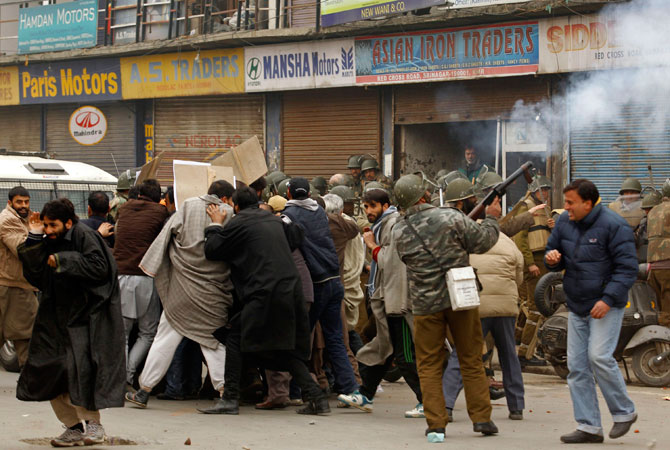 An Indian policeman releases tear gas as supporters of the Jammu Kashmir Liberation Front (JKLF) are detained in Srinagar December 7, 2012.