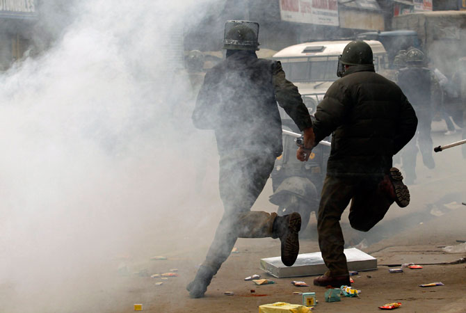 Indian policemen run for cover amid tear gas during clashes with supporters (unseen) of the Jammu Kashmir Liberation Front (JKLF) in Srinagar December 7, 2012.