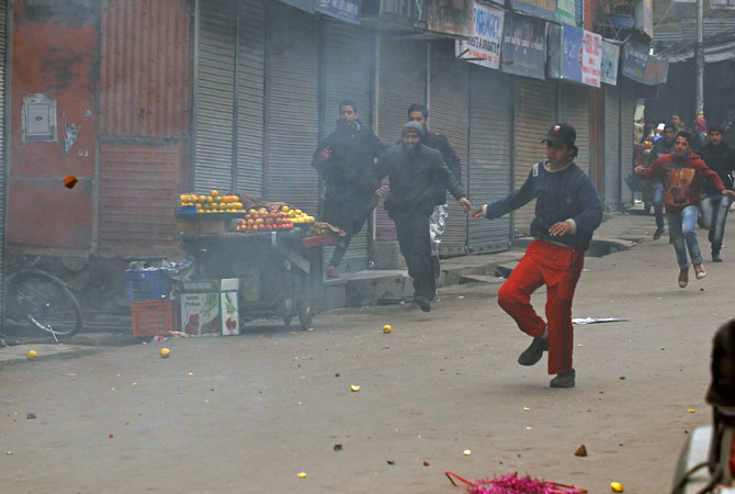 Supporters of the Jammu Kashmir Liberation Front (JKLF) chase away Indian policemen (unseen) during clashes in Srinagar December 7, 2012.