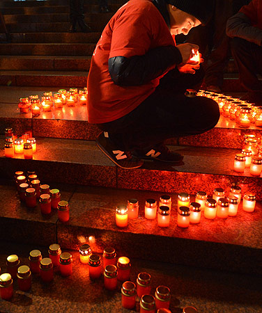 A boy lights a candle to set to a symbolic Red Ribbon during a rally in the center of the Ukrainian capital of Kiev. Ukraine has one of the fastest growing HIV/AIDS epidemics in the world. ? Photo by AFP