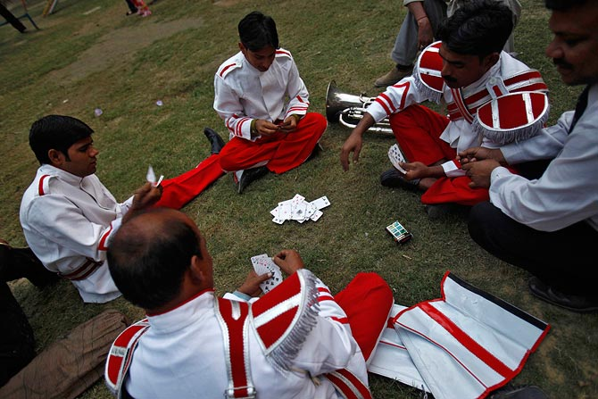 Members of a brass band play cards as they wait to perform.