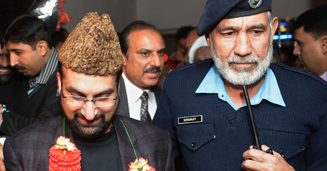 Leader of the moderate All Parties Hurriyat Conference Mirwaiz Umar Farooq (L) comes out from airport upon his arrival in Islamabad on December 15, 2012. - Photo by AFP