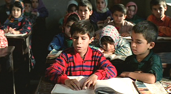 Mohamed, reading out in his sister's classroom and everyone watching him closely.
