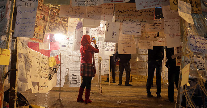 An Egyptian woman visits an installation made of political art and slogans in Cairo's Tahrir Square.—AFP Photo