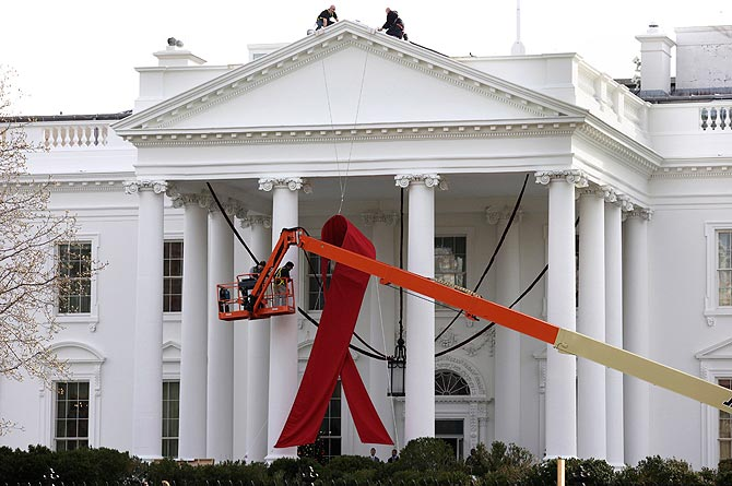 A large red ribbon is installed on the North Portico of the White House in Washington November 30, 2012. ? Photo by Reuters