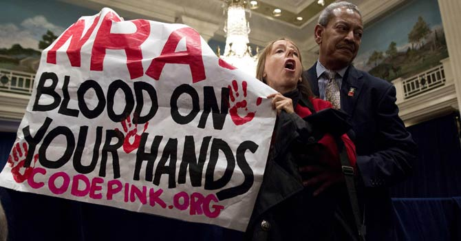 A protester, holding up a sign, is removed by a security guard during a speech by Wayne LaPierre (unseen), executive vice president of the National Rifle Association (NRA), during a news conference in Washington Dec 21, 2012.  - Reuters