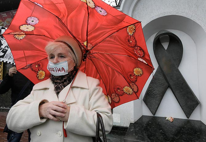 A Ukrainian woman wearing a medical mask demonstrates in front of the memorial monument to AIDS victims in Kiev, Ukraine. An estimated 230,000 Ukrainians, or about 0.8 percent of people aged 15 to 49 in a population of 46 million, are living with HIV, the virus that causes AIDS. Some 120,000 are in urgent need of anti-retroviral therapy, which can greatly prolong and improve the quality of their lives. But due to a lack of funds, less than a quarter are receiving the drugs, one of the lowest levels in the world. ?