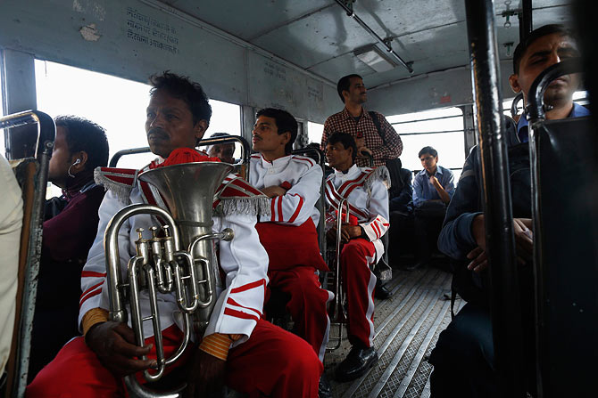Members of a brass band sit on a bus on their way to perform.