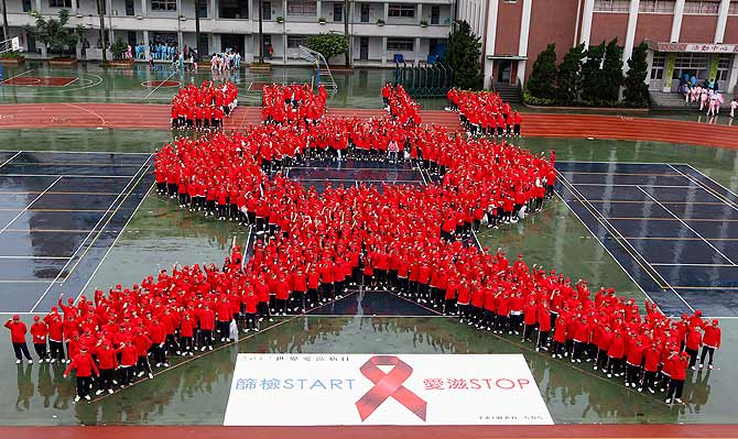 Students form a giant red ribbon during a publicity campaign to promote awareness about HIV/AIDS in Taipei. ? Photo by Reuters