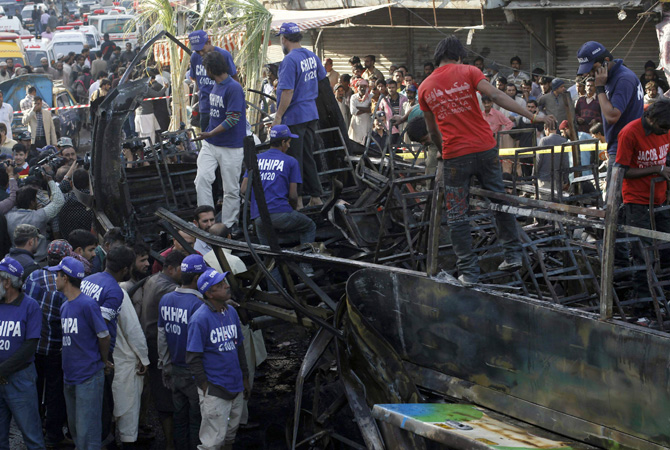 Rescuers search for body parts in a bus after a bomb explosion in Cantonment area, Karachi December 29, 2012. A bomb went off on a bus in the southern Pakistani city of Karachi on Saturday killing six people and wounding 48, police and a hospital official said.?Photo by Reuters