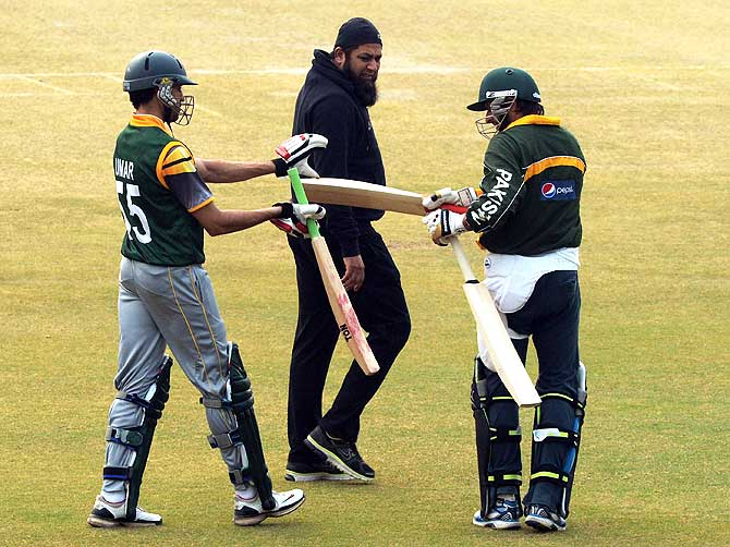 Shahid Afridi and Umar Gul exchange bats as Inzamam-ul-Haq looks on. ? Photo by AFP