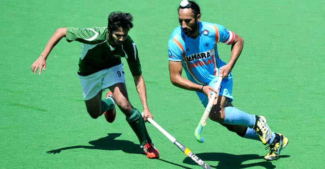 Pakistan's Abdul Haseem Khan and Sardar Singh vie for the ball during the bronze-medal match at the FIH Champions Trophy 2012 in Australia. Pakistan and India will face off once again in the Asian Champions Trophy on December 24 in Doha, Qatar.  – File photo by AP