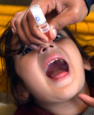 A Pakistani polio vaccination worker gives polio vaccine drops to a young girl in Peshawar. ? Photo by AFP