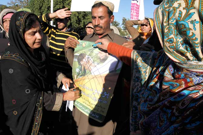 A woman from the All Pakistan Lady Health Workers Welfare Association draws crosses over an anti-polio drive poster, signalling a boycott of the ongoing campaign due to security concerns. ? Photo by Reuters