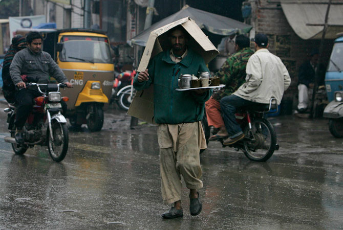 A street tea seller covers his head with a cardboard sheet as he walks in the rain to deliver tea to customers after a heavy downpour in old Lahore.
