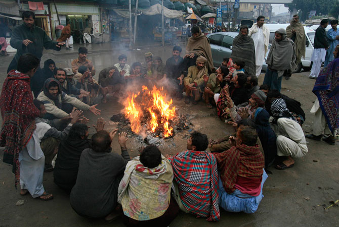 Labourers sit around a fire to keep themselves warm by a roadside after a downpour in Lahore.