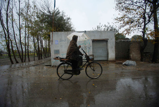 A man rides a bicycle as he holds an umbrella to protect himself from rain in Peshawar.