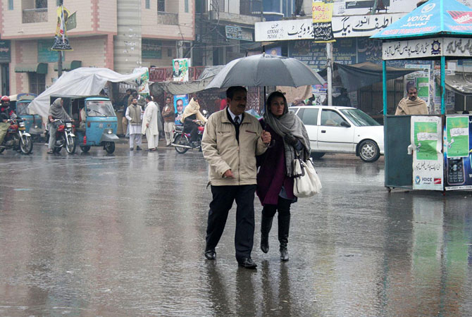 Commuters on the road during heavy rain in Faisalabad.