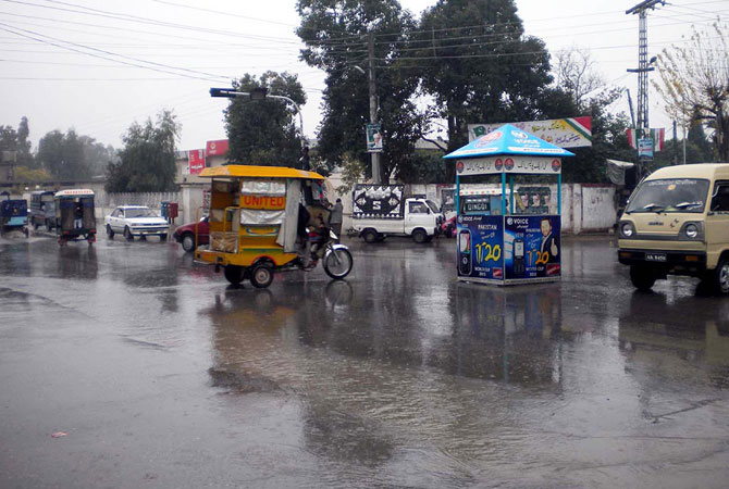 Motorists on the road during rain in Attock.