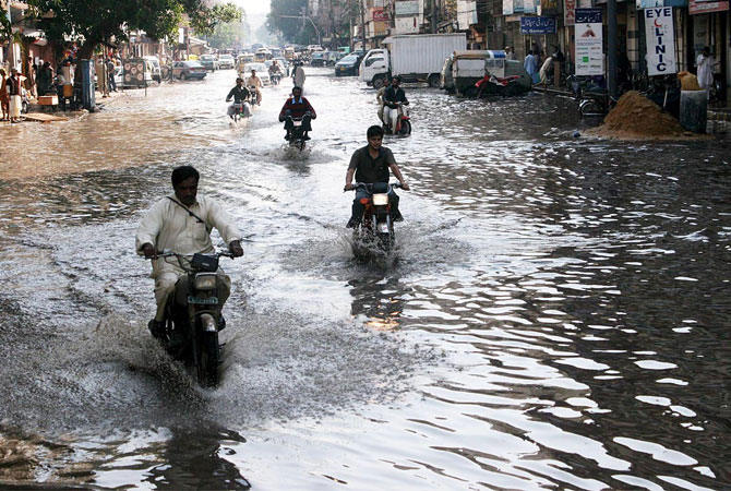 Motorists wade through rainwater accumulated on Light House Road after rain in Karachi.