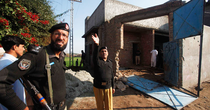 Security force officers are seen near the house where Taliban militants took refuge during a gun battle in Peshawar December 16, 2012. - Photo by Reuters