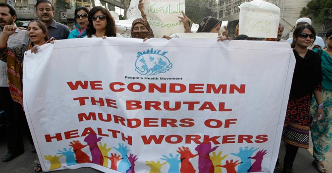 Activists rally in Karachi to condemn killings of health workers. -AP Photo
