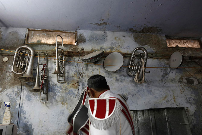 Musical instruments hang on the wall of a basement as a member of a brass band gets ready.