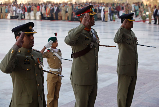 Commandant Pakistan Military Academy (PMA), Major General Sadiq Ali (2nd R), salutes during the guard mounting ceremony at the mausoleum of Mohammad Ali Jinnah in Karachi December 25, 2012. A contingent of PMA cadets mounted the guard at the mausoleum of Mohammad Ali Jinnah to mark his 136th birth anniversary.
