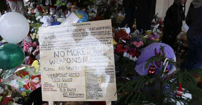 A sign against weapons is displayed at a memorial to the Newtown shooting victims in the Sandy Hook village of Newtown, Conn., Saturday, Dec 22, 2012.  The funerals for the victims of the school shooting are wrapping up after a wrenching week of farewells. Twenty children and six adults were killed at Sandy Hook Elementary School on Dec 14.  Adam Lanza, the lone gunman, killed his mother before going on the rampage and then committed suicide. - AP Photo