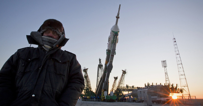 A security guard stands in front of the Soyuz TMA-07M spacecraft as it is lifted to its launch pad at the Baikonur cosmodrome December 17, 2012. The Soyuz spacecraft, which will carry U.S. astronaut Thomas Marshburn, Russian cosmonaut Roman Romanenko and Canadian astronaut Chris Hadfield, is scheduled to fly to the International Space Station on December 19. The air temperature dropped to minus 32 degrees Celsius (minus 25.6 degrees Fahrenheit) at Baikonur on Monday morning. REUTERS/Shamil Zhumatov  (KAZAKHSTAN - T