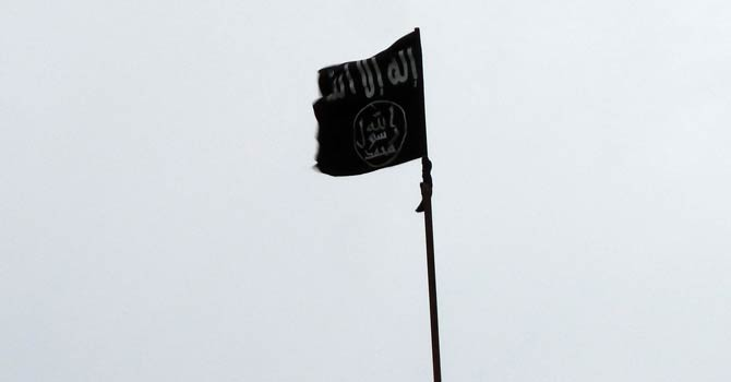 A black flag, trademark of jihadists, is hoisted over one of the buildings in the Sheikh Suleiman base, some 25 kilometres northwest of the city of Aleppo on Dec 9, 2012. - AFP Photo