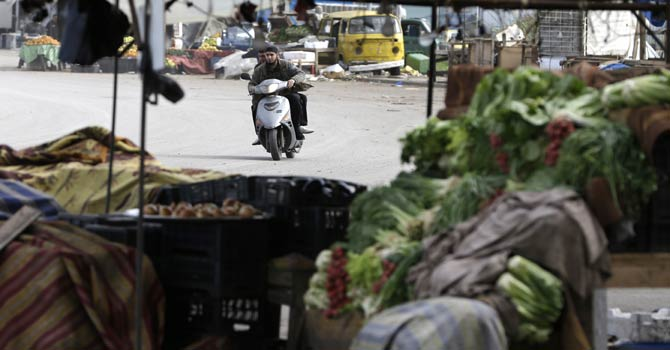 Lebanese citizens, seen through a deserted vegetable stand, ride their scooter as they cross a street to avoid sniper fire during clashes that erupted between pro and anti-Syrian regime gunmen in the northern port city of Tripoli, Lebanon, Wednesday, Dec 5, 2012. Gunmen loyal to opposite sides in neighbouring Syria's civil war battled in the streets of northern Lebanon and the death toll from two days of fighting was at least five killed and 45 wounded, officials said. The fighting comes at a time of deep uncertainty in Syria, with rebels closing in on President Bashar al-Assad's seat of power in Damascus. - AP Photo