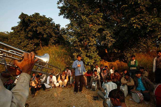 Members of a brass band practice in an empty space outside a residential area in New Delhi.