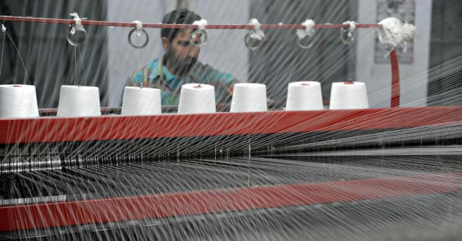 A Pakistani man prepares threads at a textile factory in Gujrat