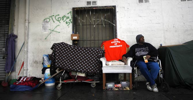 A homeless man sits across the street from where the Skid Row Housing Trust's 102 pre-fabricated 350 square foot modular apartments are under construction downtown, becoming the first housing complex of its type for the homeless in the nation, in Los Angeles, California, Dec 18, 2012. - Reuters