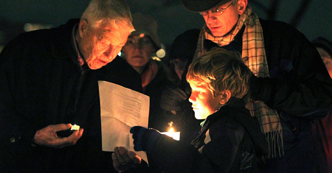 "Nine-year-old Jack Noble (C) of Seattle reads the names of the victims of the Sandy Hook Elementary School shooting at a candlelight vigil at Green Lake Park in Seattle December 15, 2012. Twelve girls, eight boys and six adult women were killed in the shooting on Friday at the Sandy Hook Elementary School in Newtown, Connecticut, the state's chief medical examiner said on Saturday. Dressed in ""cute kid stuff,"" all 20 children died when heavily armed 20-year-old gunman Adam Lanza forced his way into their school, Sandy Hook Elementary, and shot them and six women in an act of violence that has shattered their once-tranquil suburban town. - Photo by Reuters"