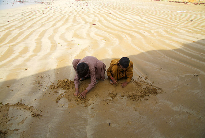 Brothers building dreams in sand.
