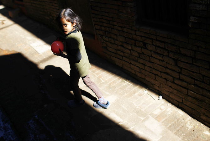 A Nepalese girl walks in an alley at Bhaktapur, Nepal, Friday, Jan. 25, 2013.
