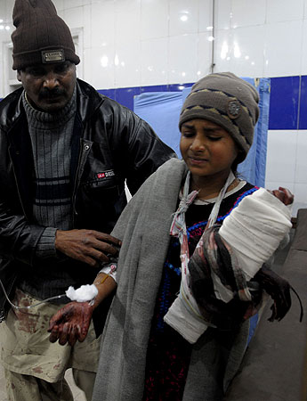 A Pakistani man helps an injured train passenger girl at a hospital after an attack on the Jaffar Express train, in Quetta on early Sunday morning 6, 2012. – Photo by AFP