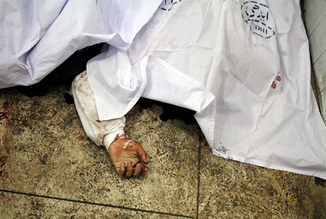 A hand is seen under a sheet at a hospital morgue after the second bomb explosion in Quetta January 10, 2013. – Photo by Reuters