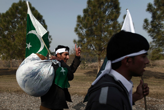 A supporter of Muhammad Tahirul Qadri, leader of Mihaj-ul-Quran, carries his blanket as he arrives to take part in a protest in Islamabad January 14, 2013. ? Photo by Reuters