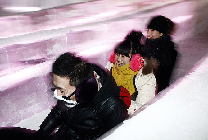 Visitors sliding down an ice slide in Ice and Snow World at the opening ceremony of the 2013 Harbin International Ice and Snow Festival in Harbin, in northeast China's Heilongjiang province. ? AFP Photo