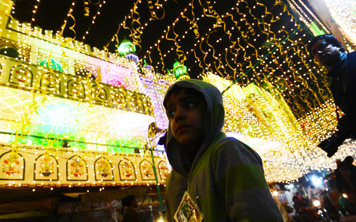 Pakistani pedestrians cross an illuminated street to mark the celebration Eid Milad-un-Nabi in Lahore. ?Photo by AFP