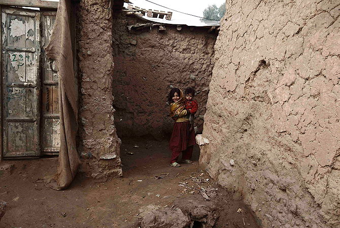 A girl smiles as she carries her brother in a slum on the outskirts of Islamabad January 8, 2013.  ? Reuters Photo