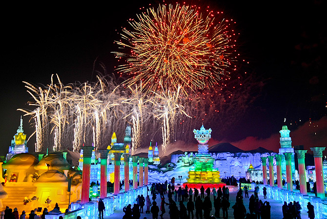 Visitors watch fireworks explode over ice sculptures during the official opening of the 29th Harbin International Ice and Snow Festival in Harbin in northeast China's Heilongjiang. ? AP Photo