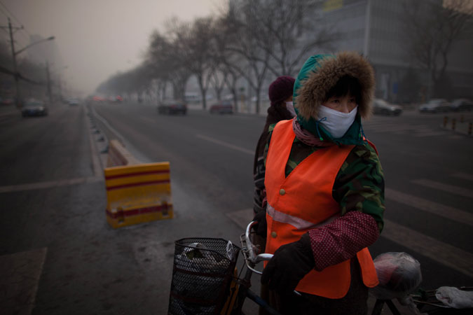 A cyclist wearing a mask prepares to cross a road in the severe pollution of Beijing. ?Photo by AFP