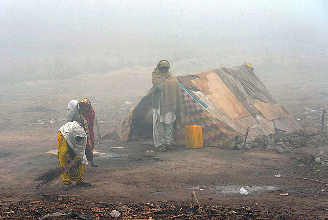 A Pakistani homeless family stands outside their tent on a cold and foggy day at a slum area of Peshawar on January 7, 2013.  Several major cities of Pakistan have been engulfed by thick fog causing traffic problems and flight cancellations. ? AFP Photo