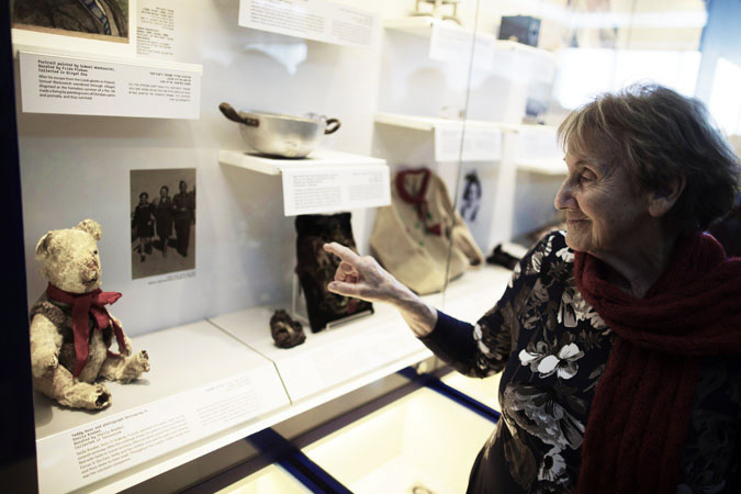Stella Knobel, an 80-year-old Holocaust survivor from Krakow in Poland, points to the teddy bear she had received on her seventh birthday before fleeing to Russia, on display at the Yad Vashem Holocaust museum in Jerusalem. ?Photo by AFP