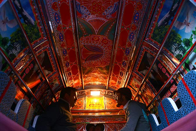 Commuters travel in a decorated minivan in Rawalpindi on January 20, 2013. Many trucks, buses and vans in Pakistan are highly customized and decorated by their owners. These adorned vehicles are considered as moving art, or jingle art, with vehicle owners paying as much as 2,000 USD on decorations. — AFP Photo